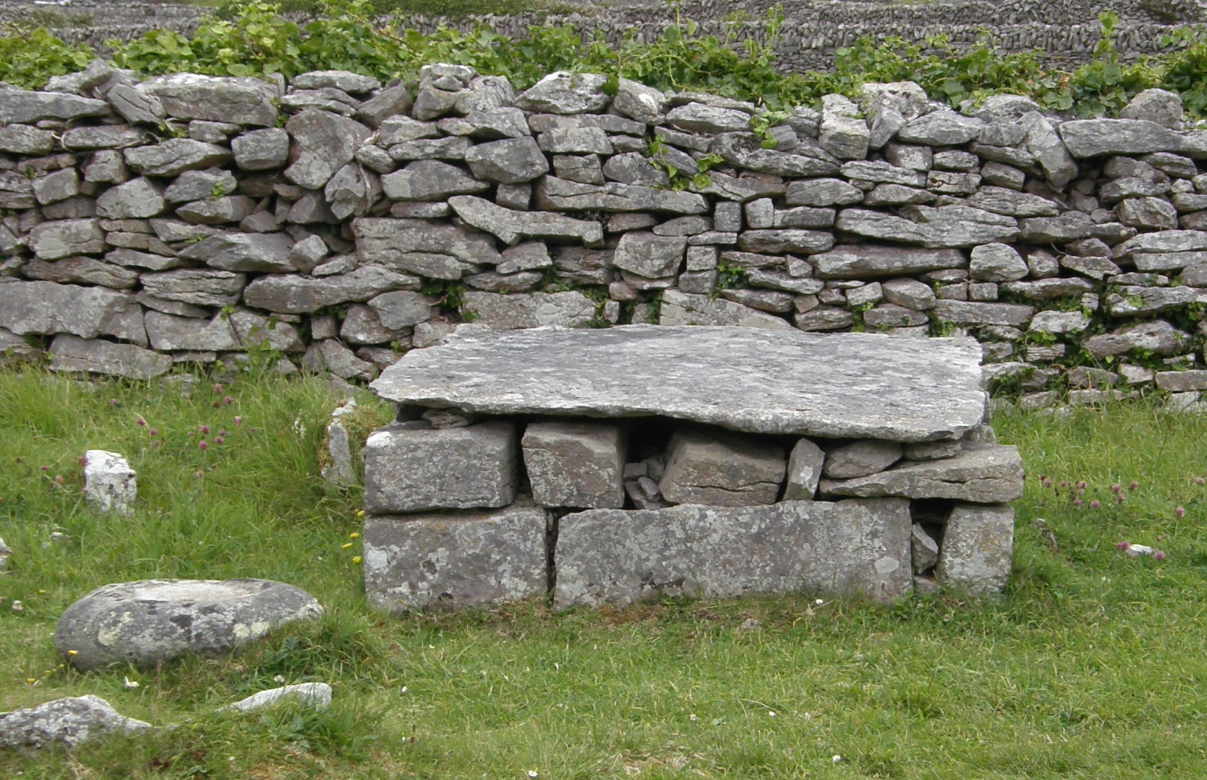 Stone altar outside St. Gobnait's Church and Bullaun Stone