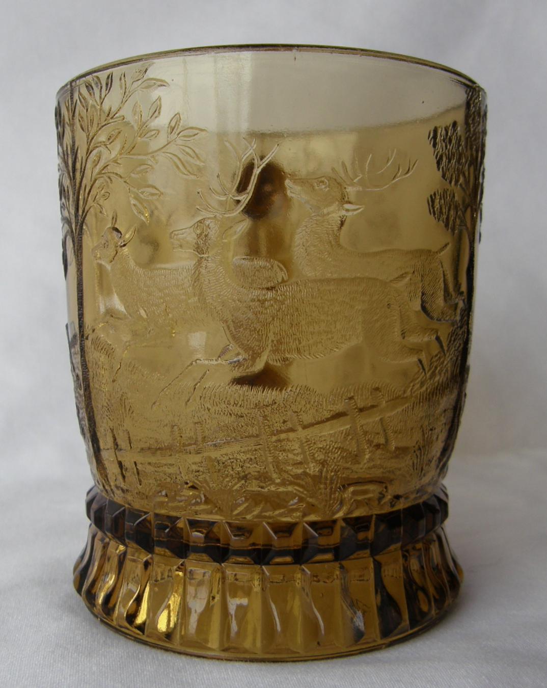 """Dog Chasing Deer (Size: 3-1/4"""" dia. x 3-3/4"""" ht.; Color: Amber) Directly opposite the handle, sculpting shows a doe and two stags running from the dog further around the bowl of the mug.."""