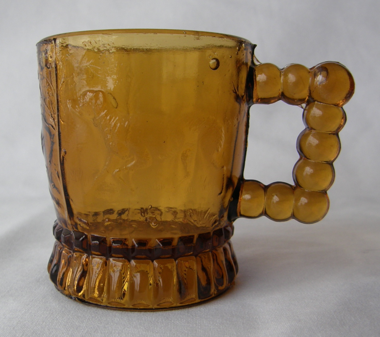 """Pointing Dog (Size: 2-3/8"""" dia. x 2-5/8"""" ht.; Color: Amber) To the right of the handle, sculpting shows a hunting dog looking straight ahead and pointing toward the bird."""