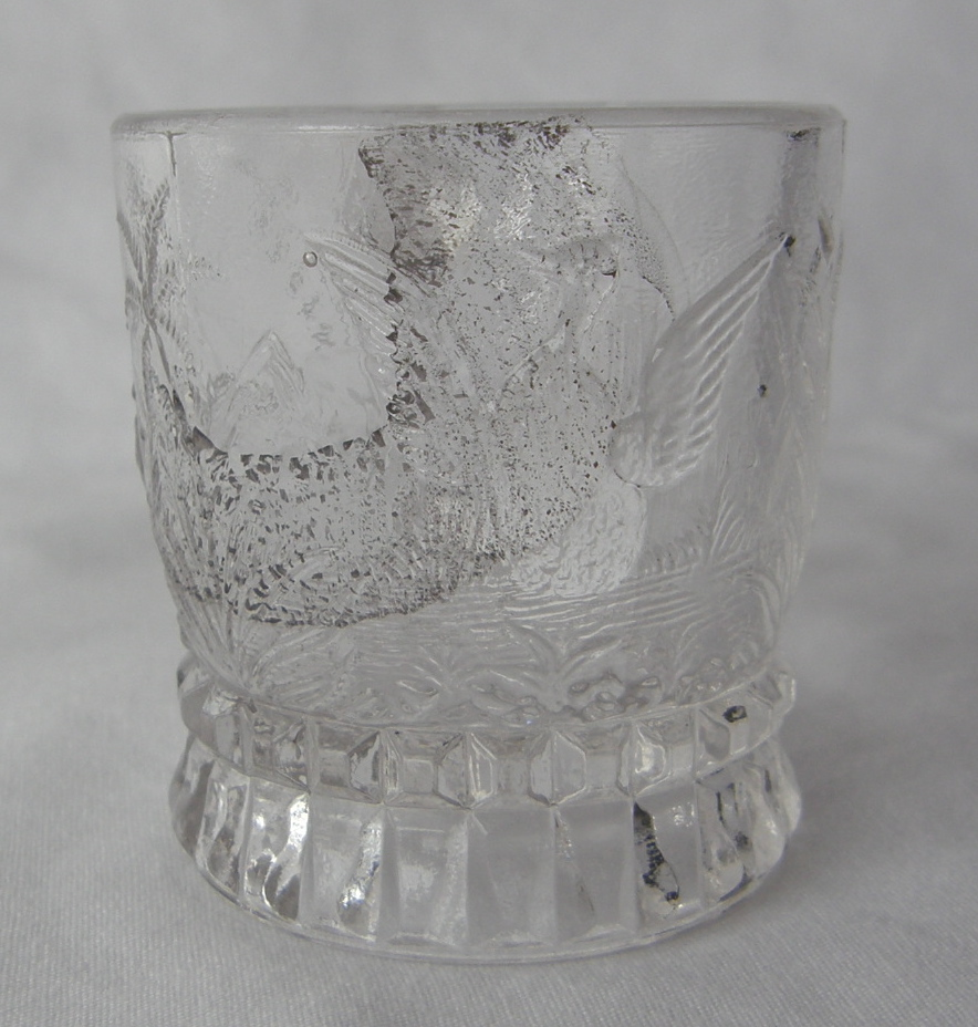 """Swan - aka Water Fowl, U.S. Glass No. 3802, or Federal's No. 3802 (Size: 1-7/8"""" dia. x 2"""" ht.; Color: Clear) Directly opposite from the handle, sculpting shows a duck or goose taking flight from among water grasses. Impurities in the glass obscure the sculpted image."""