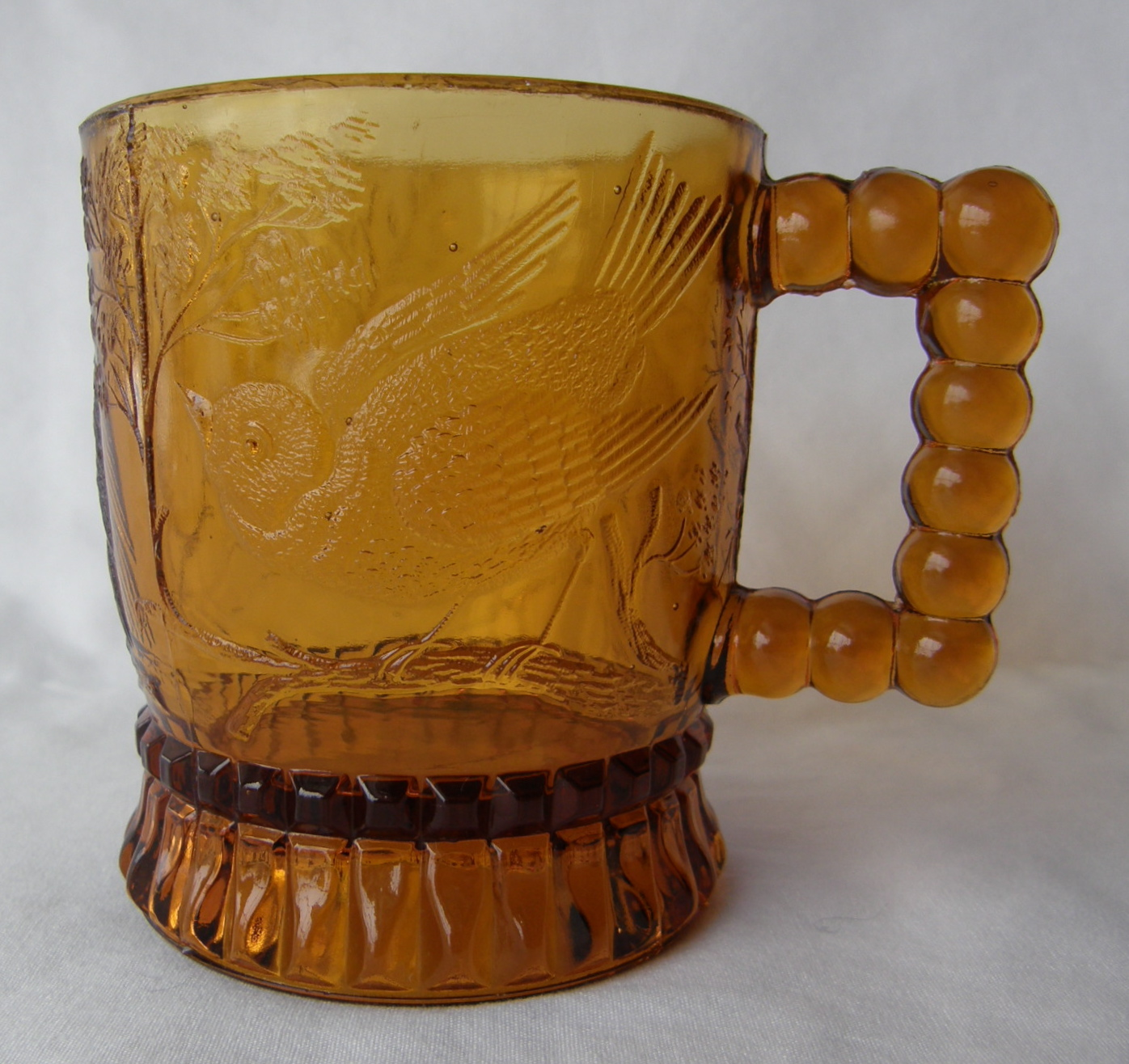 """Bird on a Branch (Size: 2-7/8"""" dia. x 3-3/8"""" ht.; Color: Amber) To the left of the beaded handle, the sculpting shows a crouching song bird perched on a branch."""