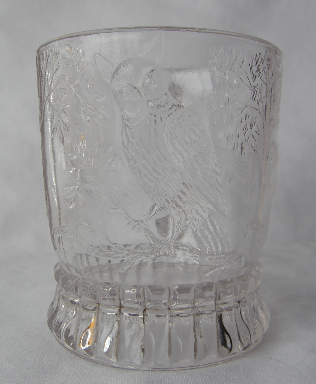 """Bird on a Branch (Size: 2-7/8"""" dia. x 3-3/8"""" ht.; Color: Clear) Directly opposte from the beaded handle, the sculpting shows an on owl perched on a branch."""