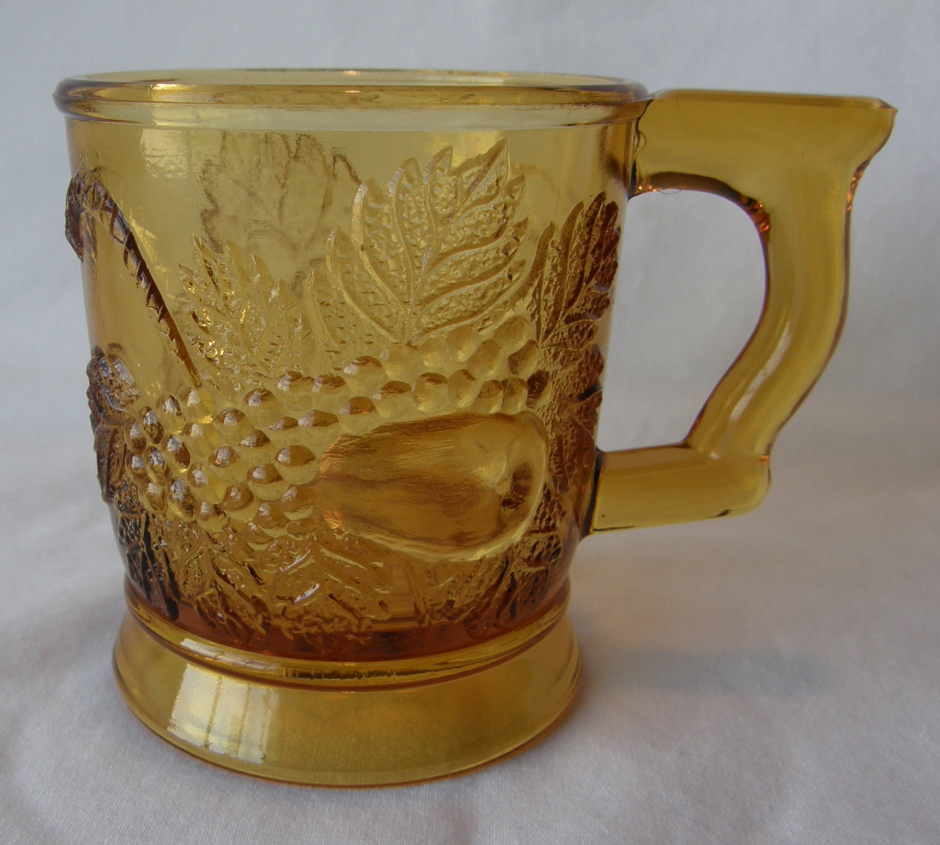 """Strawberry & Pear; handle at right; pear side showing (size: 3"""" diamater x 3-3/8"""" height; color: amber)"""